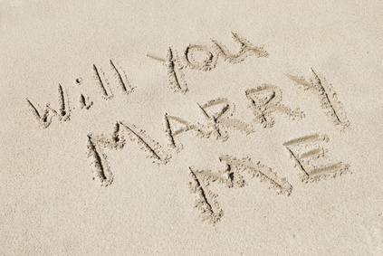 "The words ""Will You Marry Me"" written in sand, horizontal with copy space"